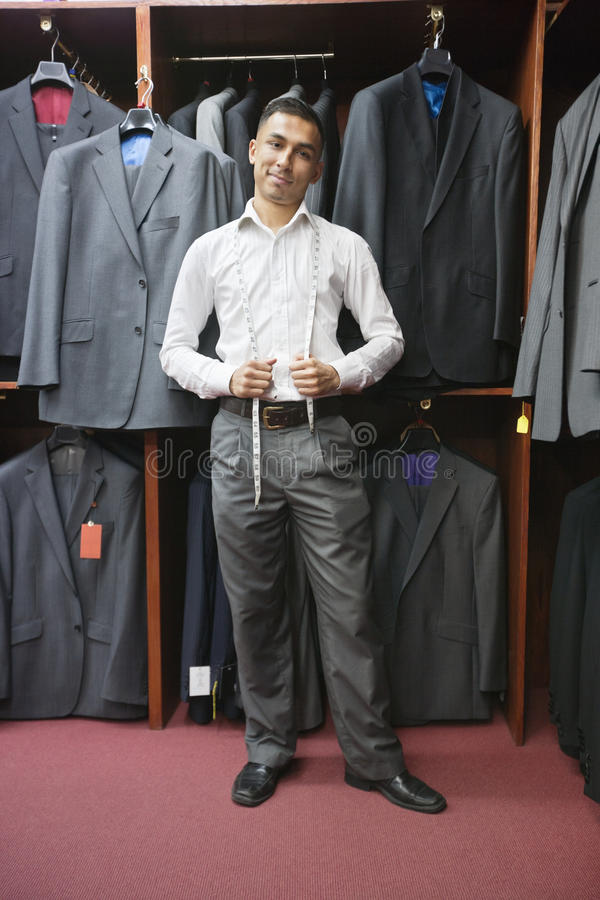 Download Portrait Of Young Man Posing With Suits Hanging In Background Stock Photo - Image of person, shop: 29669096