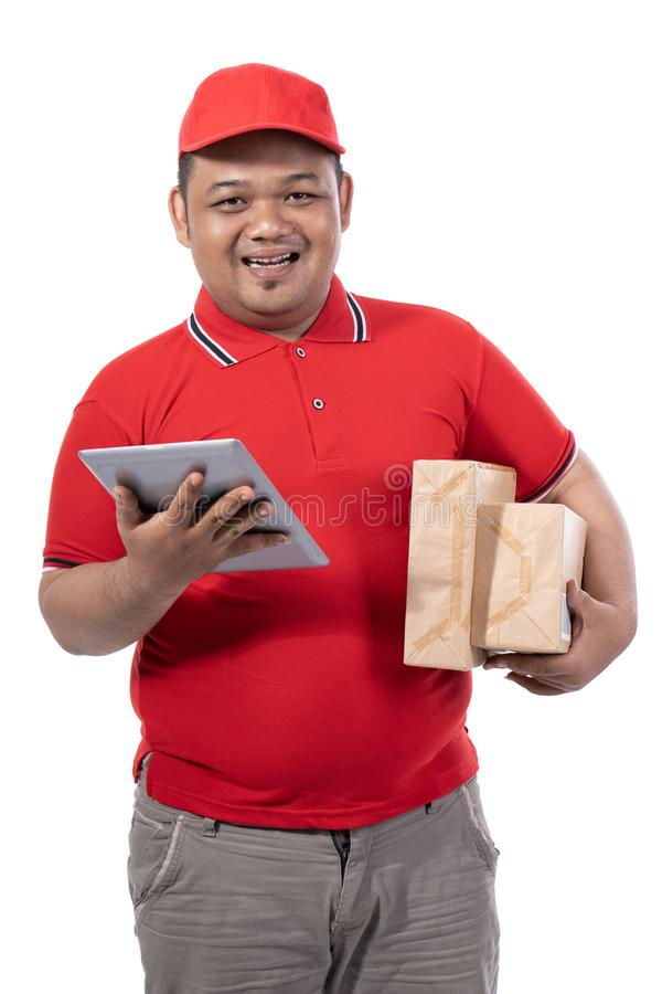 Portrait of young man with red uniform delivering boxes and holding digital tablet royalty free stock photography