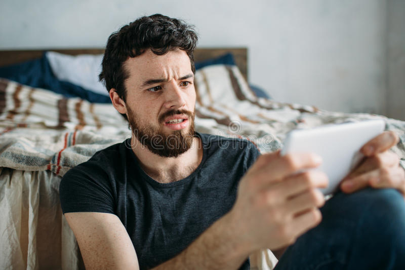 Portrait of a young man relaxing and watching a TV show on a tablet computer royalty free stock photo