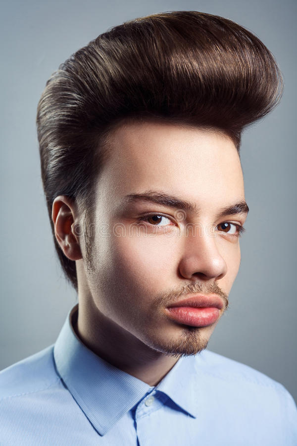 Portrait of young man with retro classic pompadour hairstyle stock image