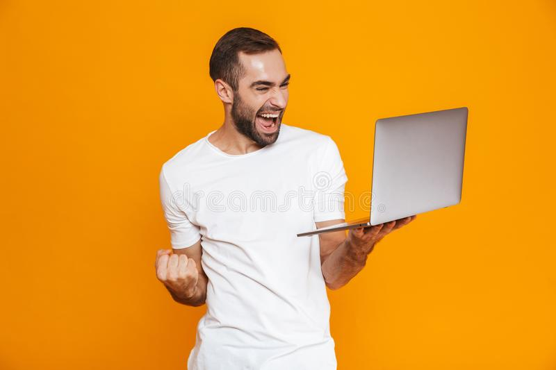 Portrait of young man 30s in white t-shirt holding silver laptop, isolated over yellow background royalty free stock image