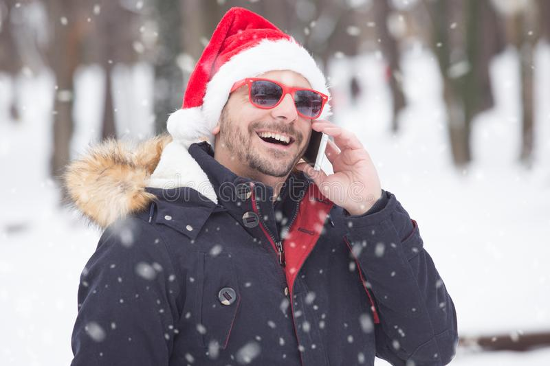 Portrait of young man with santa hat on snow day talking on smartphone. Winter concept stock photography