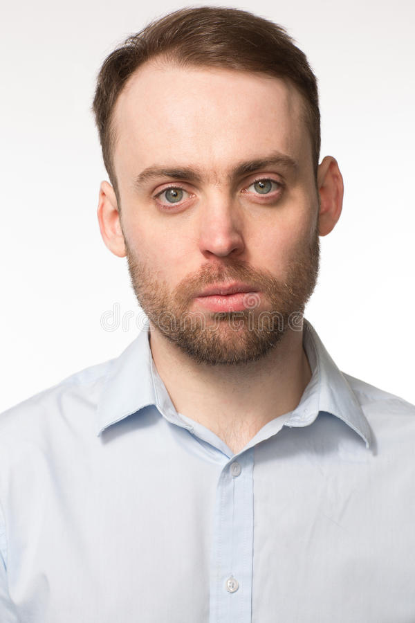 Portrait of a young man with a serious expression. Close-up portrait of a young handsome bearded Caucasian man, with blue eyes and light grey shirt, with a stock photo