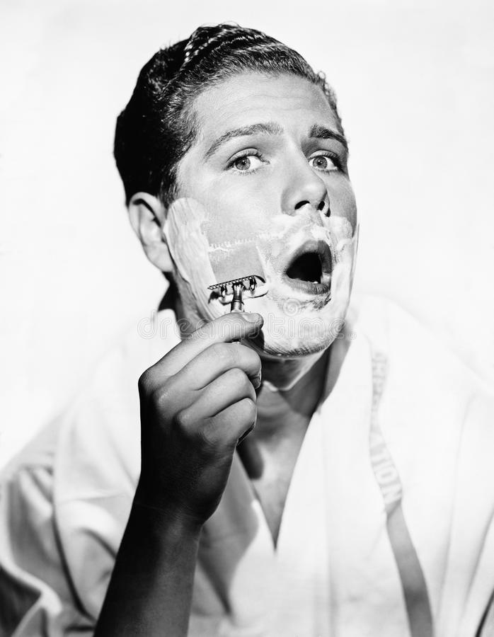 Portrait of a young man shaving royalty free stock photos