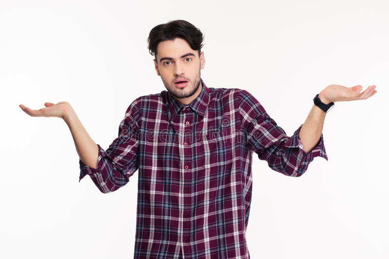 Portrait of a young man shrugging shoulders. Or holding copyspace on the palms isolated on a white background stock image