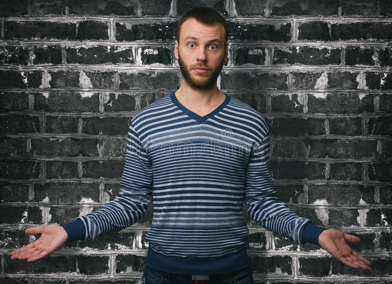 Portrait young man shrugging shoulders. What means I don`t know gesture stock image