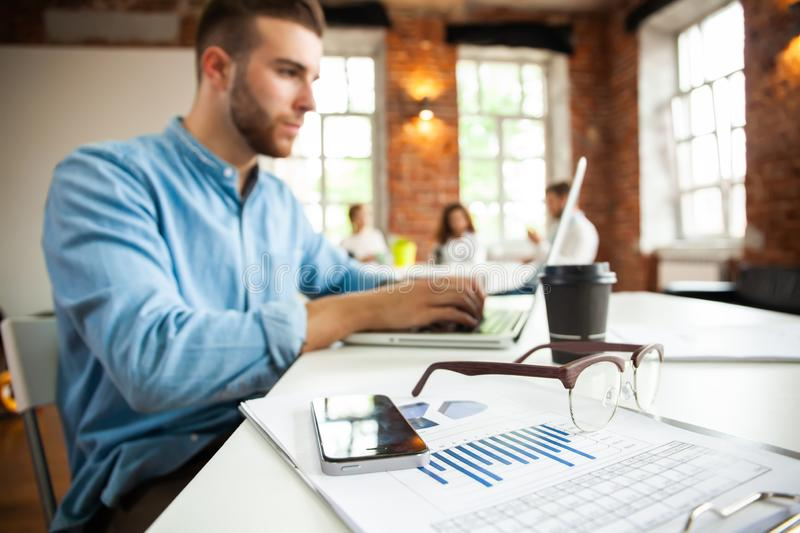 Portrait of young man sitting at his desk in the office stock photos