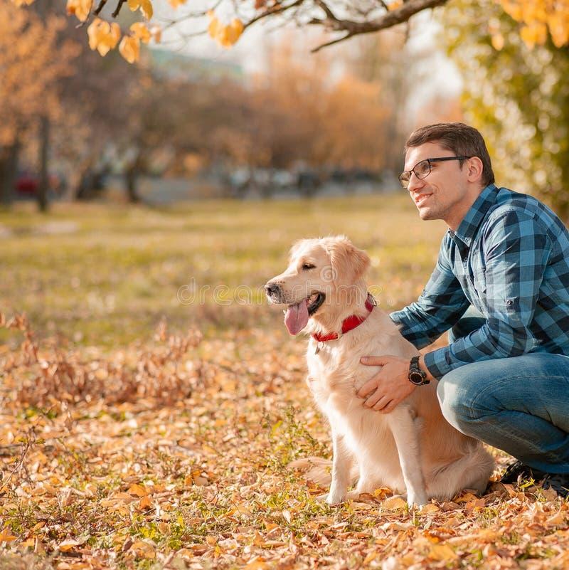 Young man hugging golden retriever dog in autumn outdoors royalty free stock photos