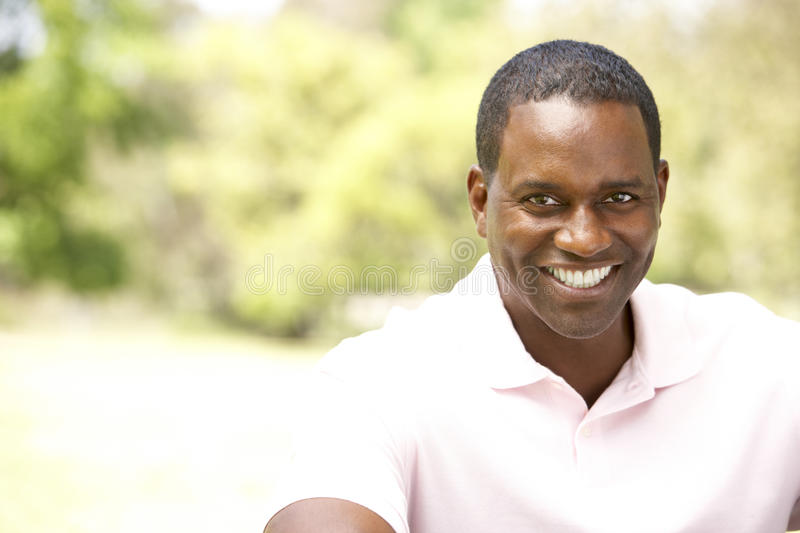 Portrait Of Young Man Sitting In Park stock photo