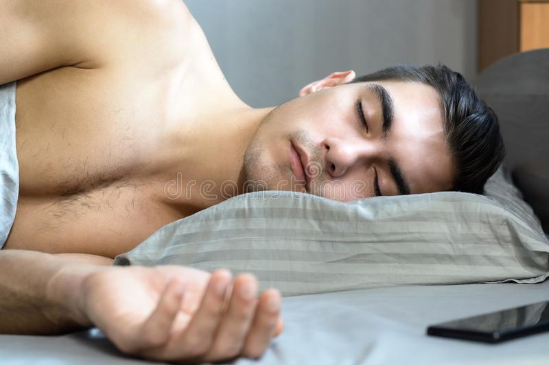 Portrait of a young man sleeping in bed on an orthopedic pillow is a special shape for a healthy spine.  royalty free stock photos