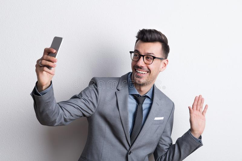 Portrait of a young man with smartphone in a studio, taking selfie. Portrait of a happy young man with smartphone in a studio, taking selfie royalty free stock photography