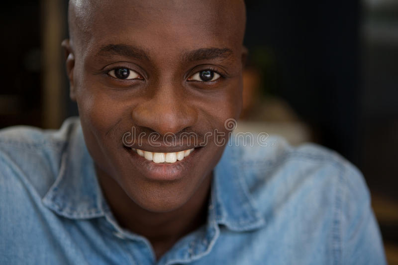 Portrait of young man smiling in coffee shop stock photography
