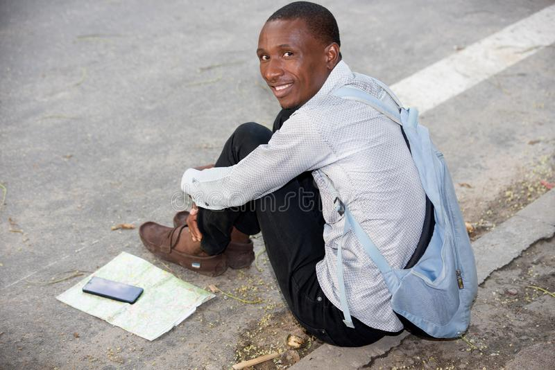Portrait of young man, smiling. Young man sitting backpack looking at camera smiling royalty free stock photos