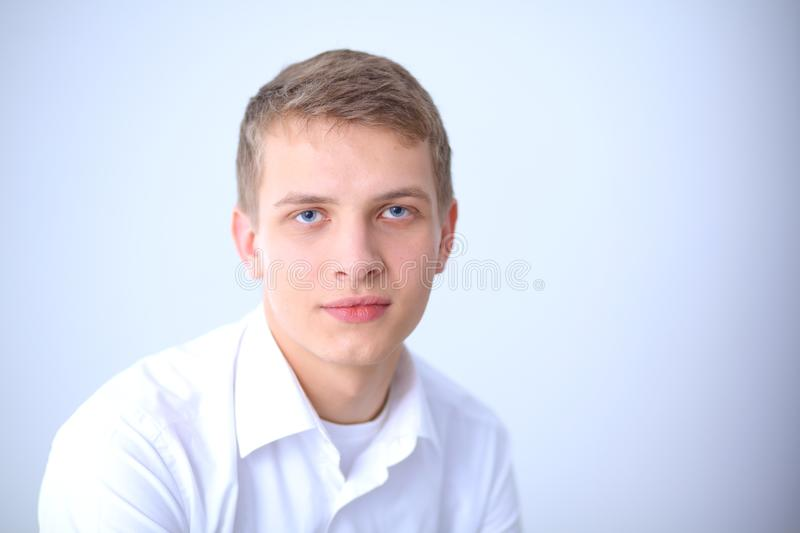 Portrait of young man smiling sitting on gray background. Portrait of young man.  stock photo