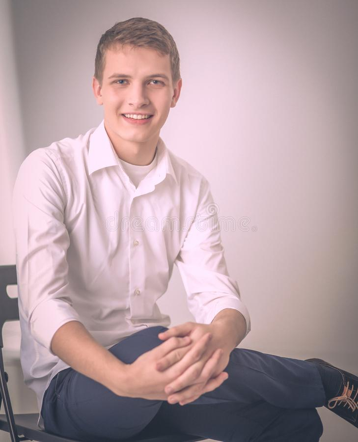 Portrait of young man smiling sitting on gray background.  stock photos