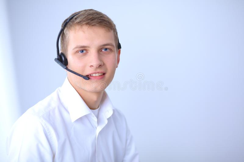 Portrait of young man smiling sitting on gray background. Portrait of young man.  royalty free stock photography