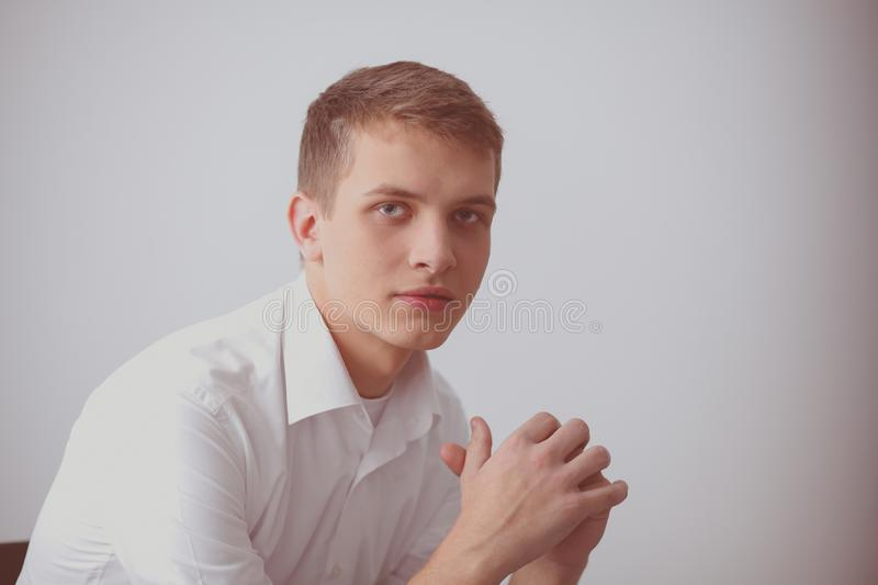 Portrait of young man smiling sitting on gray background. Portrait of young man.  royalty free stock photos
