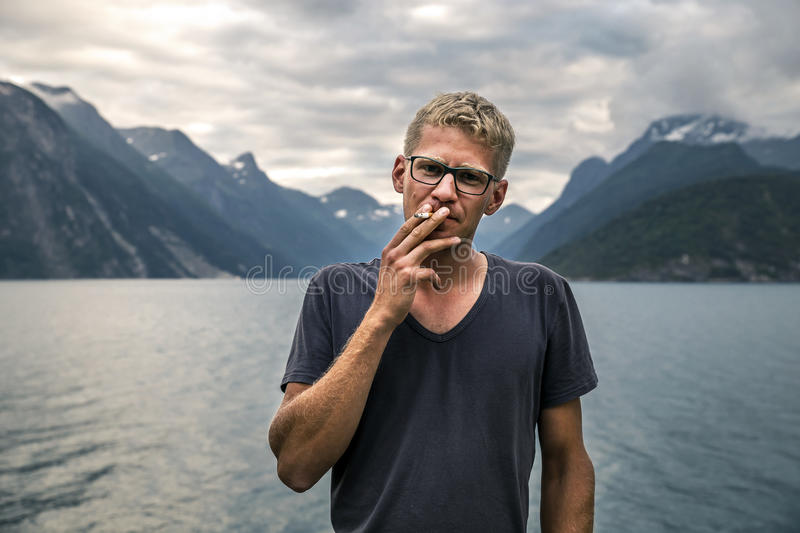 Portrait of young man smoking, close-up, Norway royalty free stock images