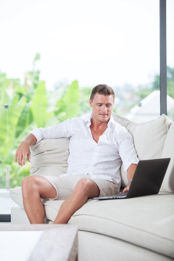 Man with comp. Portrait of young man on sofa with laptop in summer house environment royalty free stock photos