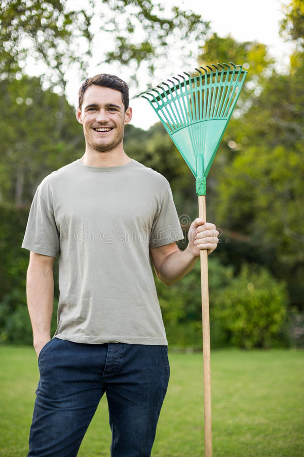 Portrait of young man standing with a gardening rake stock photography