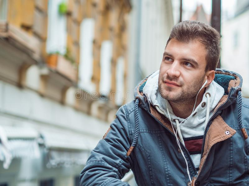 Portrait of young man in the street listening music stock photo
