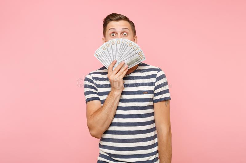 Portrait of young man in striped t-shirt holding and hiding face bundle lots of dollars, cash money, ardor gesture on. Portrait of smiling excited young man in royalty free stock photography