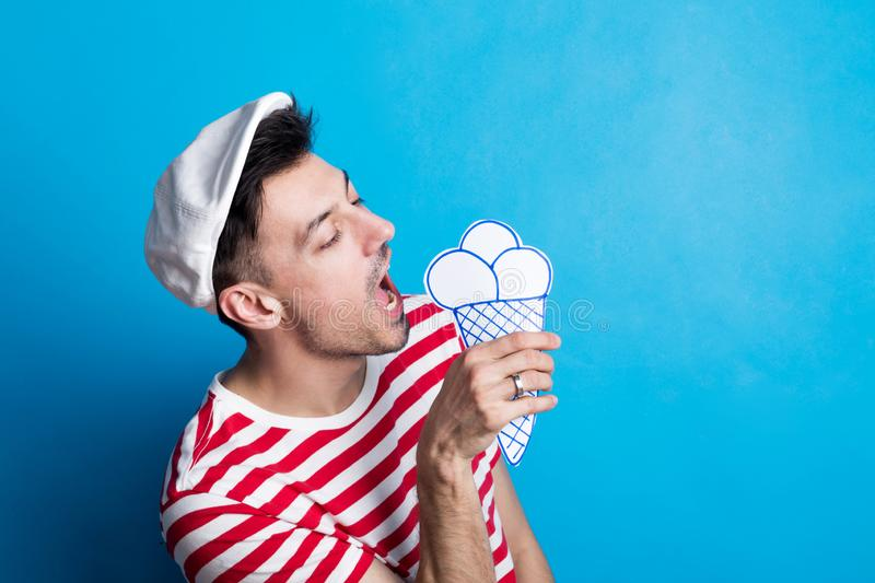 Portrait of a young man in a studio with a flat cap, eating paper craft ice cream. royalty free stock photos