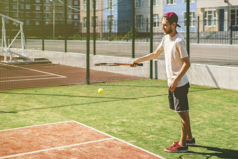 Portrait of young man on summer campus school tennis court stock photo