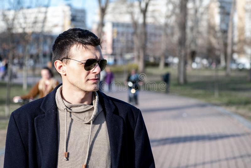Portrait of young man with sunglasses and black coat outdoor in the park stock photo