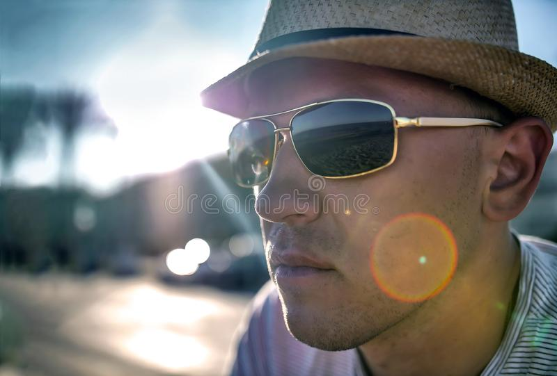 Portrait of a young unshaven man in sunglasses and hat, sun glare, close-up stock photos