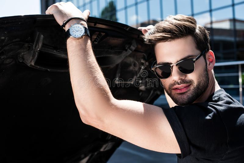 portrait of young man in sunglasses opening bonnet stock images
