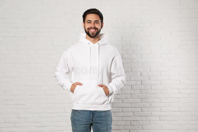 Portrait of young man in sweater at brick wall royalty free stock photos