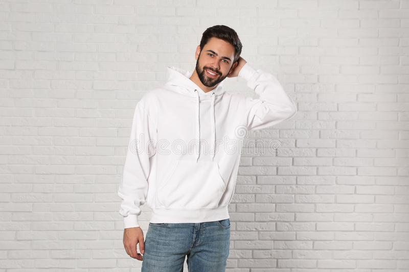 Portrait of young man in sweater at brick wall stock photography