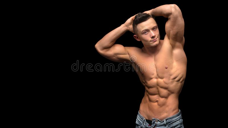 Portrait of young man with torso naked with jeans on black background stock photography
