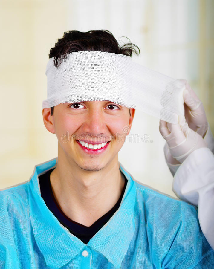 Portrait of a young man with trauma in his head and elastic bandaged around his head.  royalty free stock photo