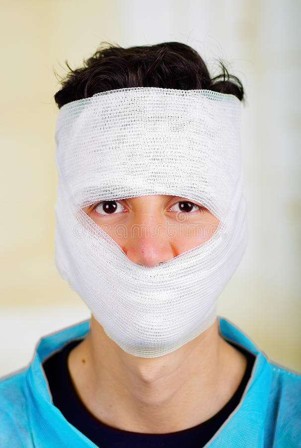 Portrait of a young man with trauma in his head and elastic bandaged around his head.  stock image