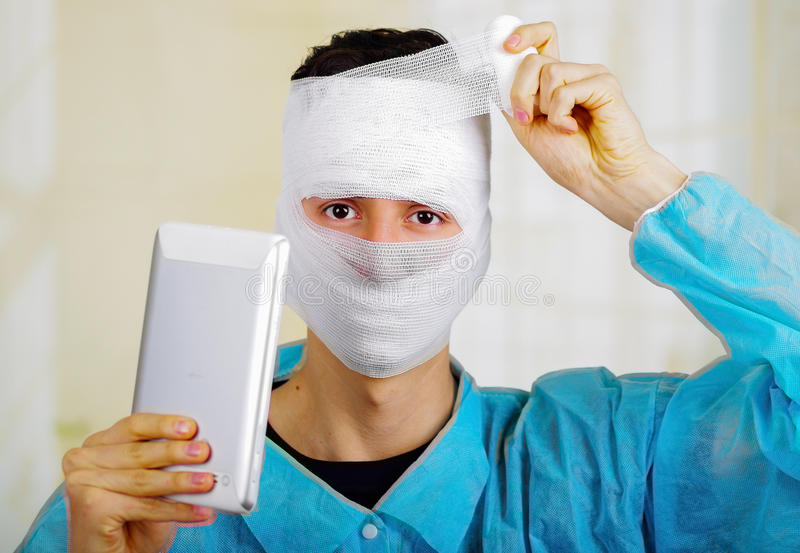 Portrait of a young man with trauma in his head and elastic bandaged around his head holding a tablet.  royalty free stock photos
