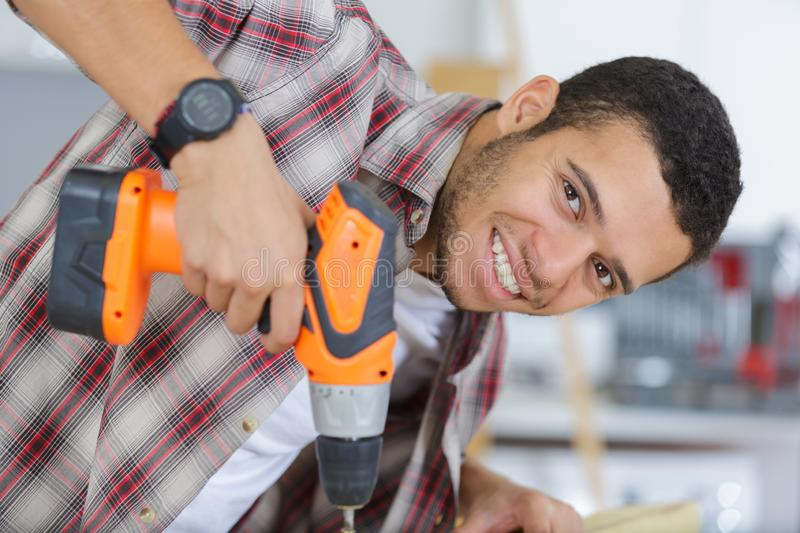 Portrait young man using drill stock photos