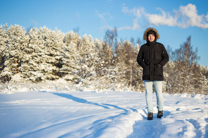 Portrait of young man walking in winter forest royalty free stock photography