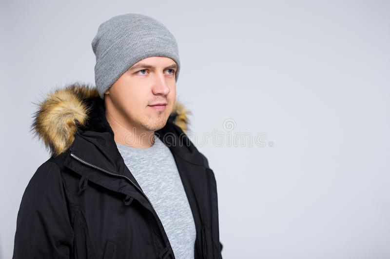 Portrait of young man in warm winter clothes over gray background royalty free stock image