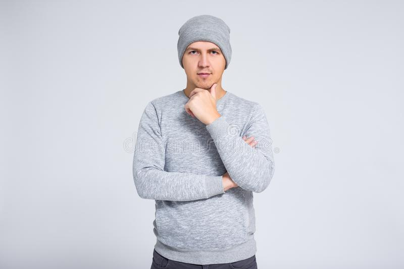 Portrait of young man in warm winter clothes thinking about something over gray stock photos