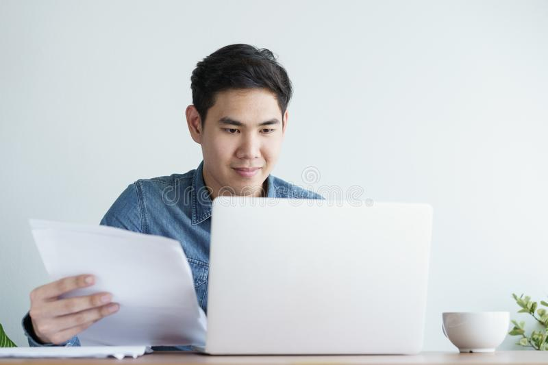 Portrait of young man wearing blue shirt is working with laptop and sitting at his desk  the office royalty free stock photos