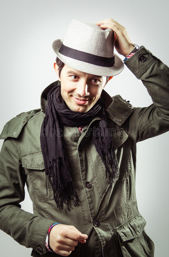 Portrait of young man wearing hat and scarf. Portrait of handsome trendy young man wearing hat and scarf on grey background royalty free stock images