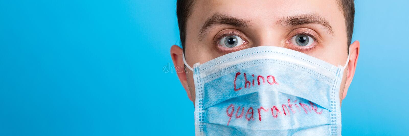 Portrait of young man wearing medical mask with China quarantine word at blue background. Coronavirus concept. Respiratory. Protection royalty free stock photography