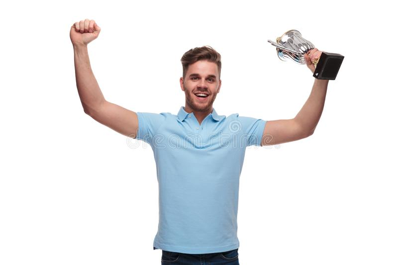Portrait of young man wearing polo shirt celebrating with trophy. Portrait of young man wearing blue polo shirt celebrating with trophy and hands in the air royalty free stock photos