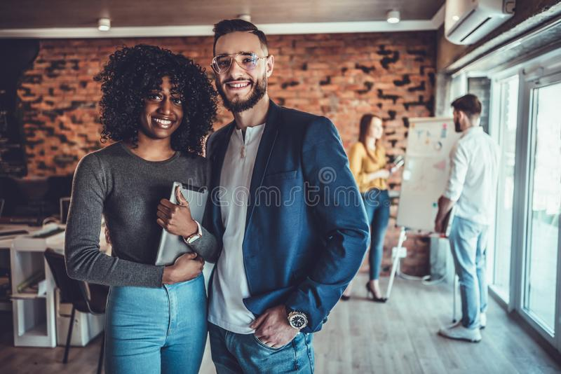 Portrait of young man and woman standing in office with colleagues meeting in background royalty free stock images