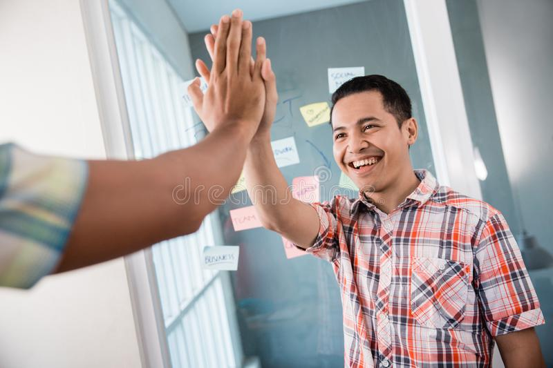 Portrait of young man worker doing high five with a partner hands when got a good idea. To broke the office problem royalty free stock image