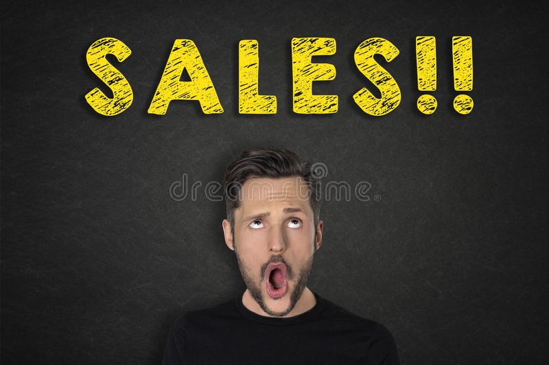 Portrait of young man with a wow expression and `Sales!!!` text royalty free stock photography