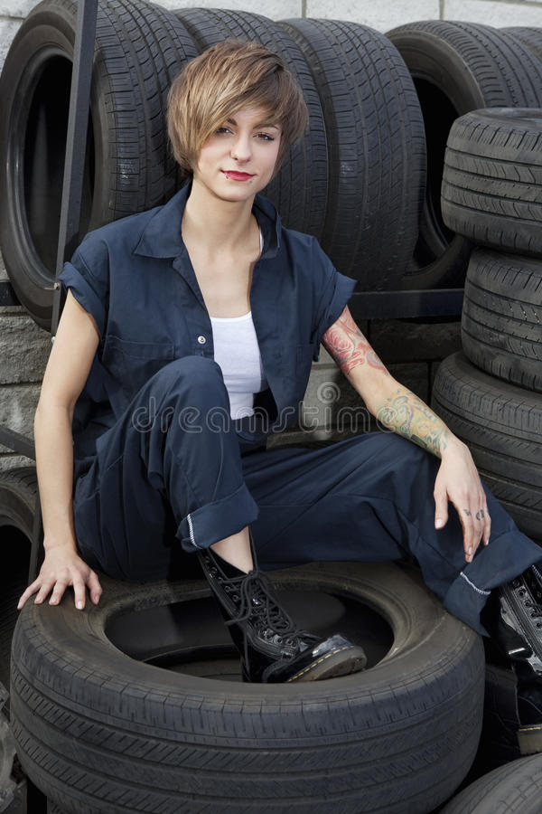 Portrait of a young mechanic sitting on tires in car workshop royalty free stock photos
