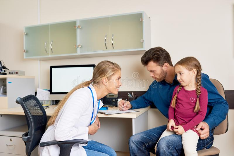 Father and Daughter Visiting Doctor stock photo